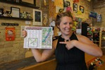 April Ripka with pad of downtown Northfield tourism maps at The Sketchy Artist