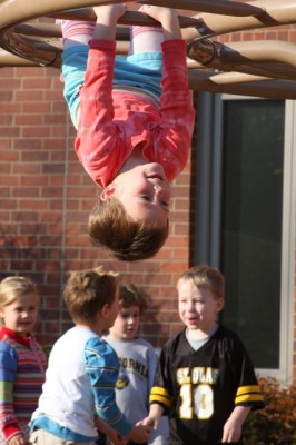 Photo: Joshua Rowan Caption: Annelise Holt, 4, dangles from the monkey bars at Open Door on Tuesday.